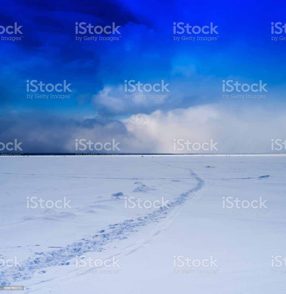 Square vivid winter morning on frozen lake footprints path cloud stock photo