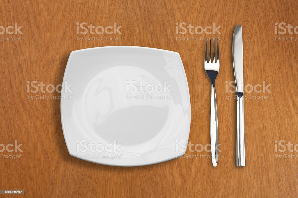 square white plate, knife and fork on wooden table stock photo