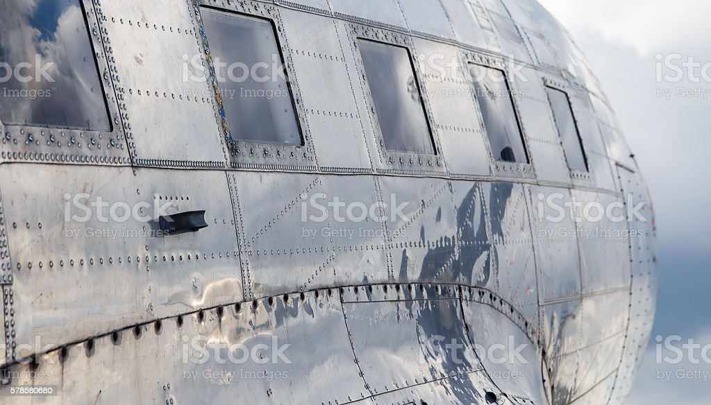 square windows old airplane  reflection sky in aluminum casing stock photo