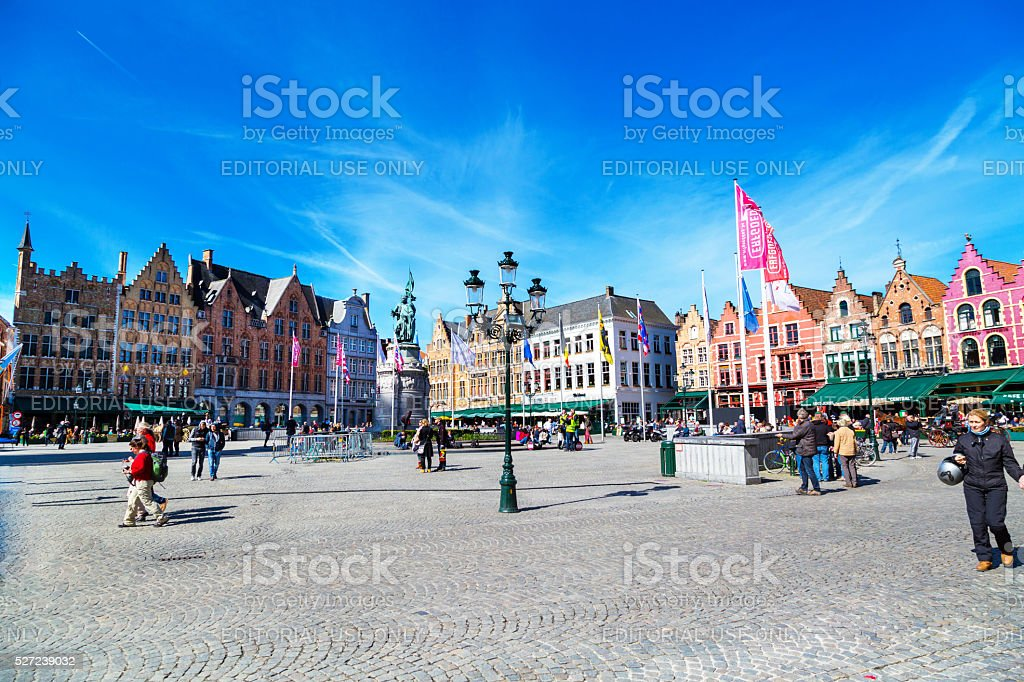 Square with colorful traditional houses, people walking in Bruges, Belgium stock photo