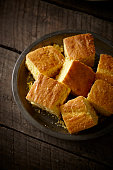Squares of cornbread in a wooden bowl