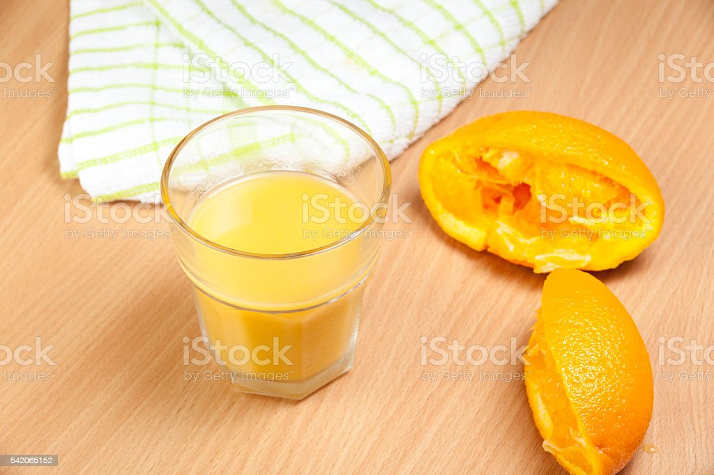 Squeezed orange halves next to a filled glass stock photo