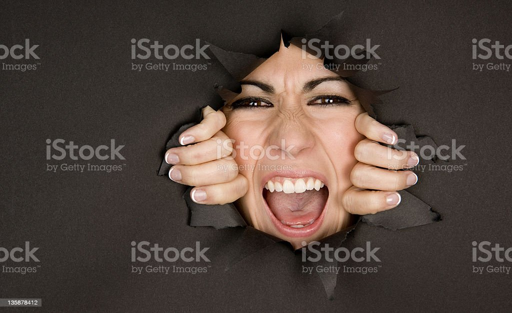 Squeezing In Face of Frustrated Woman Breaking Through Barrier royalty-free stock photo
