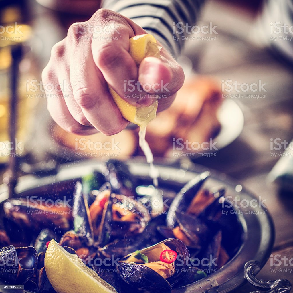 Squeezing Lemon on Classic French Mussels Dish stock photo
