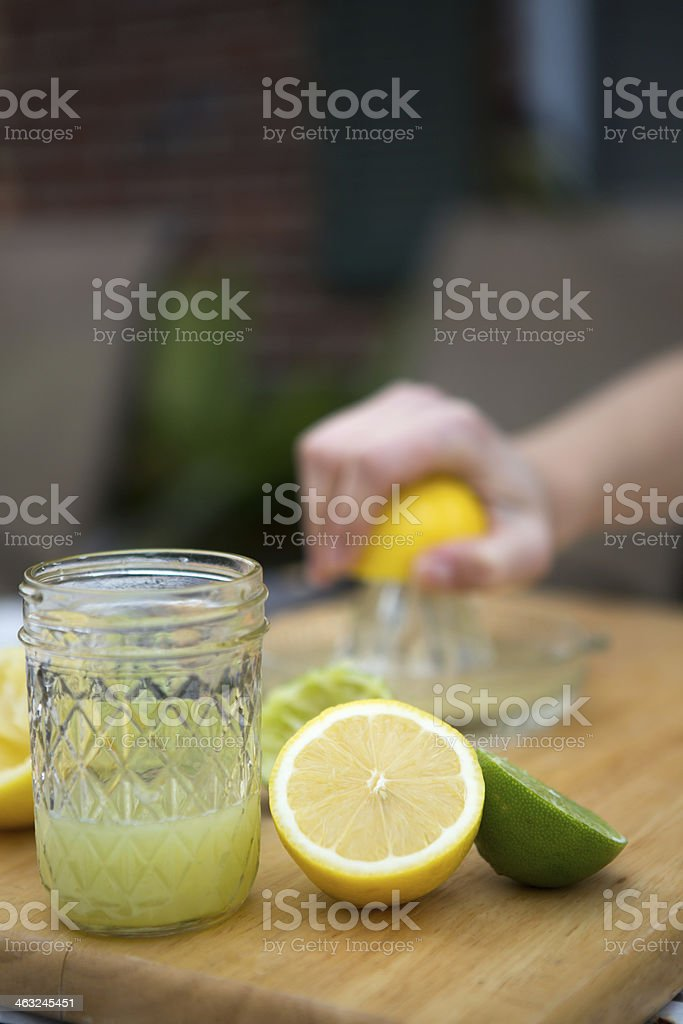 Squeezing Lemons and Limes for Juice stock photo
