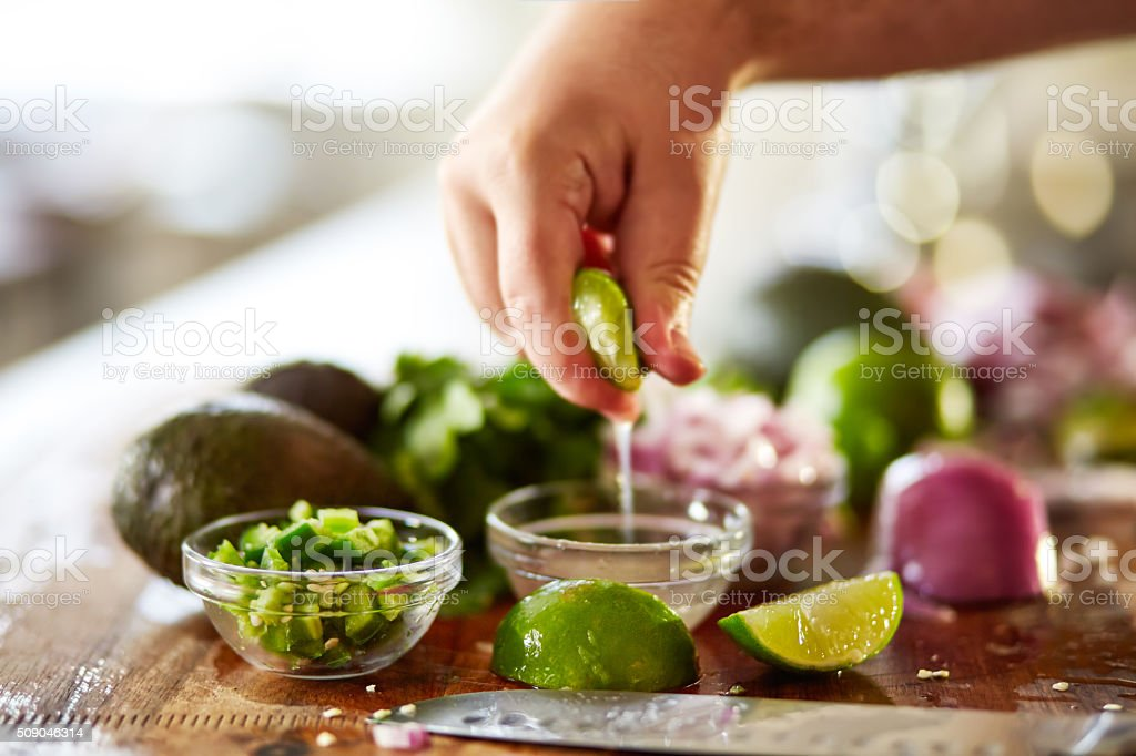 squeezing lime juice for guacamole recipe prep stock photo