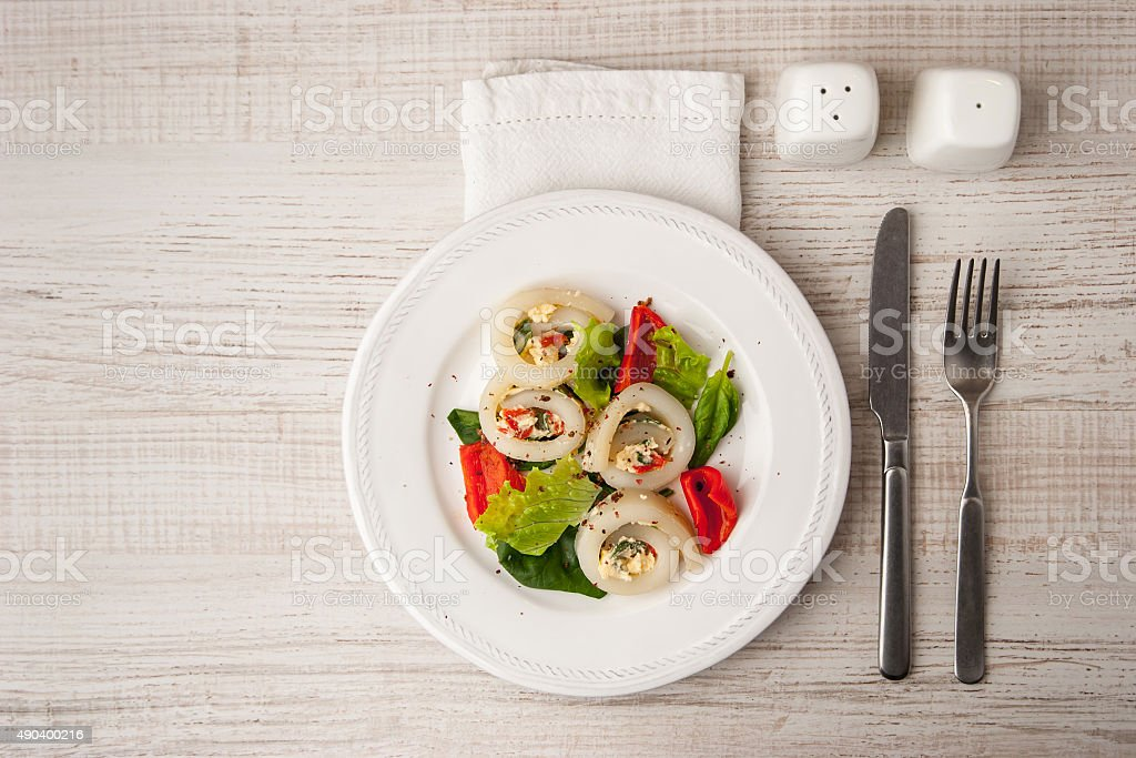 Squid roll with cheese and vegetables  with cutlery top view stock photo