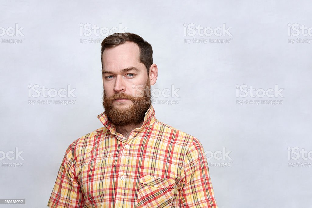 Squinting man with thick beard suspiciously looking at camera stock photo