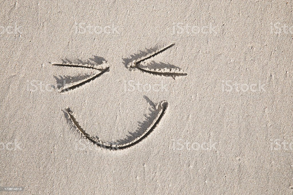 Squinty Happy Face in the Sand stock photo