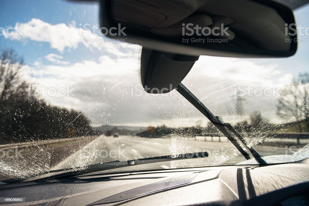Squirting fluid on a car windscreen stock photo
