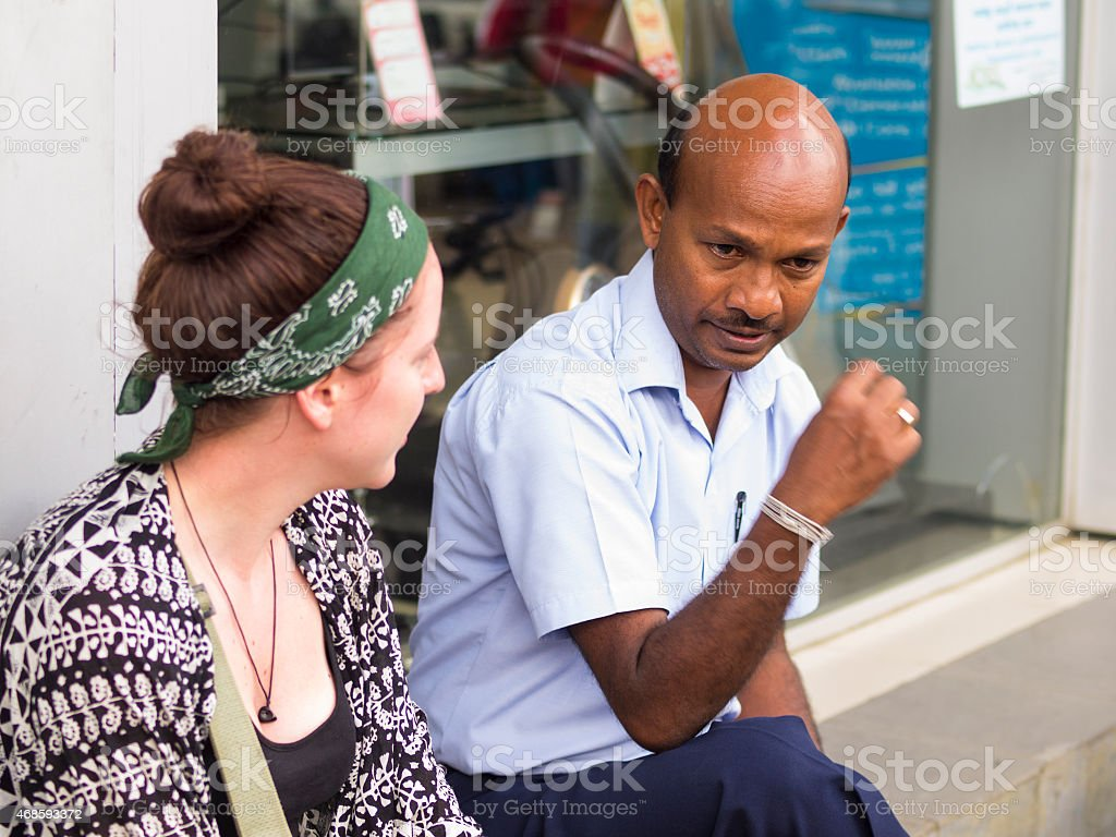 Sri Lanka man ad tourist lady at discusion stock photo