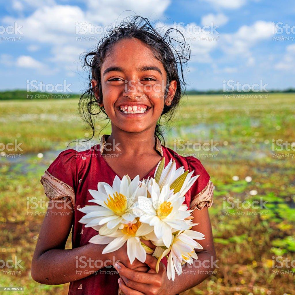 Sri Lankan little girl with lotus flowers stock photo