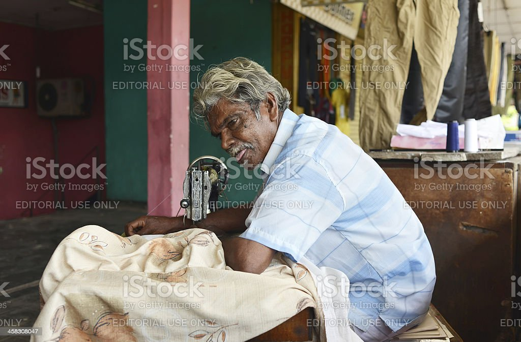 Sri Lankan man sewing in a small tailor shop royalty-free stock photo