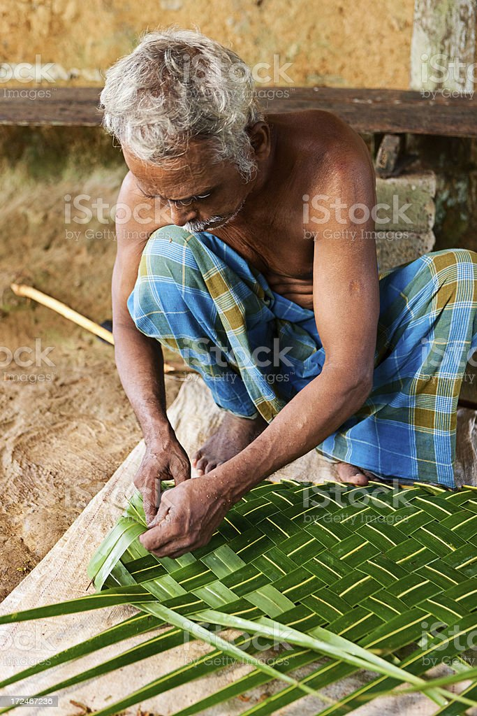 Sri Lankan man weaving palm leaf into mat royalty-free stock photo
