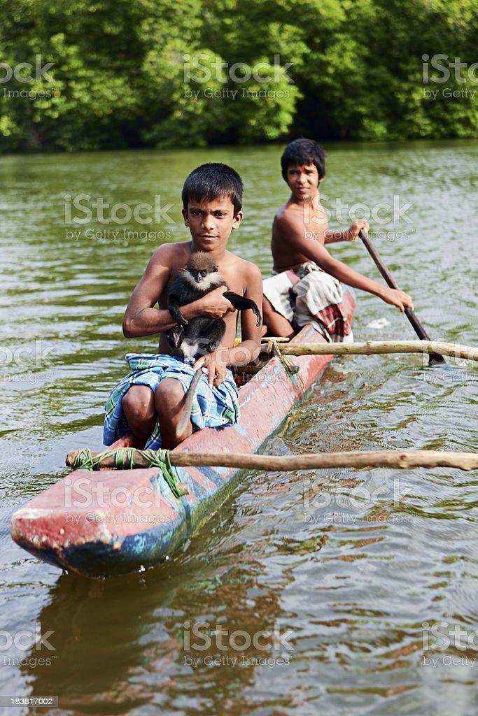 Sri Lankan young boys riding a boat on Maduganga River. royalty-free stock photo