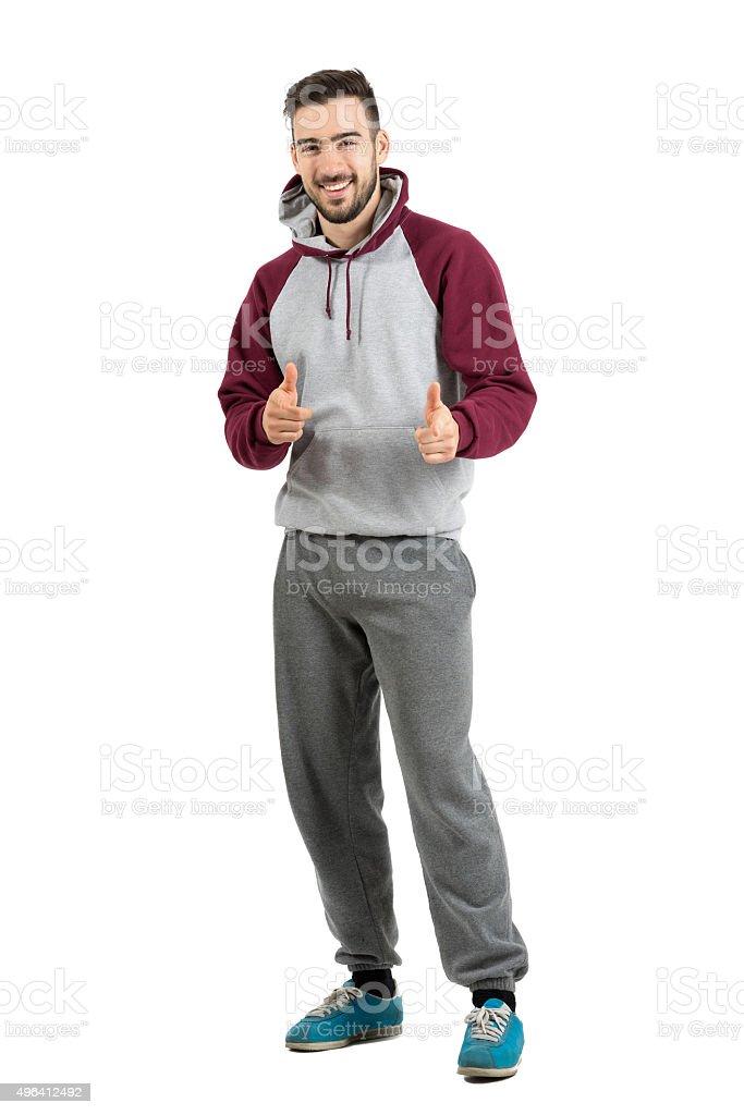 Ssmiling man in casual sportswear pointing finger gun at camera stock photo