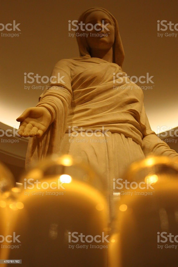 St Mary statue with candles in a Church stock photo