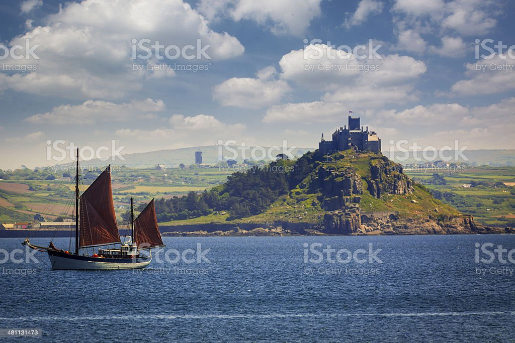 St Michael's Mount and Red-sailed Fishing Vessel stock photo