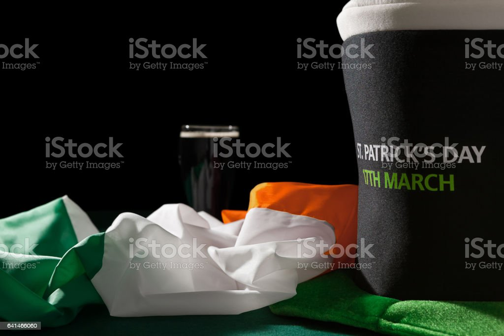 St Patrick day with a pint of black beer, hat and irish flag over a green table stock photo