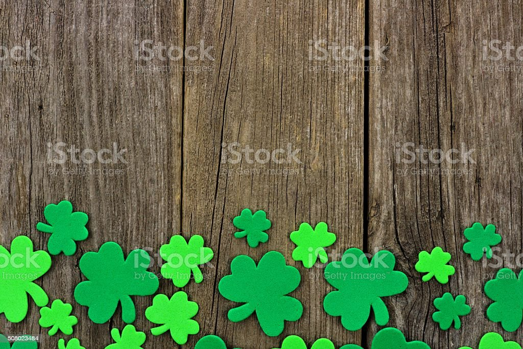 St Patricks Day bottom border of shamrocks over rustic wood stock photo