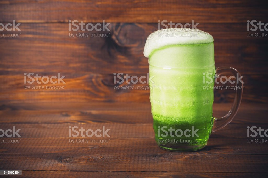 St Patrick's Day concept mug green beer against wooden background stock photo