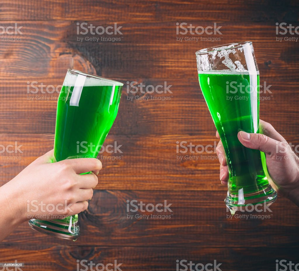 St Patrick's Day concept two mug on hands green beer against wooden background stock photo