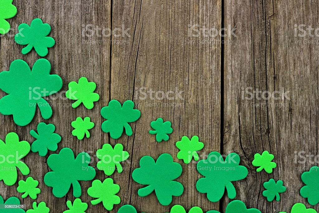 St Patricks Day corner border of shamrocks over rustic wood stock photo