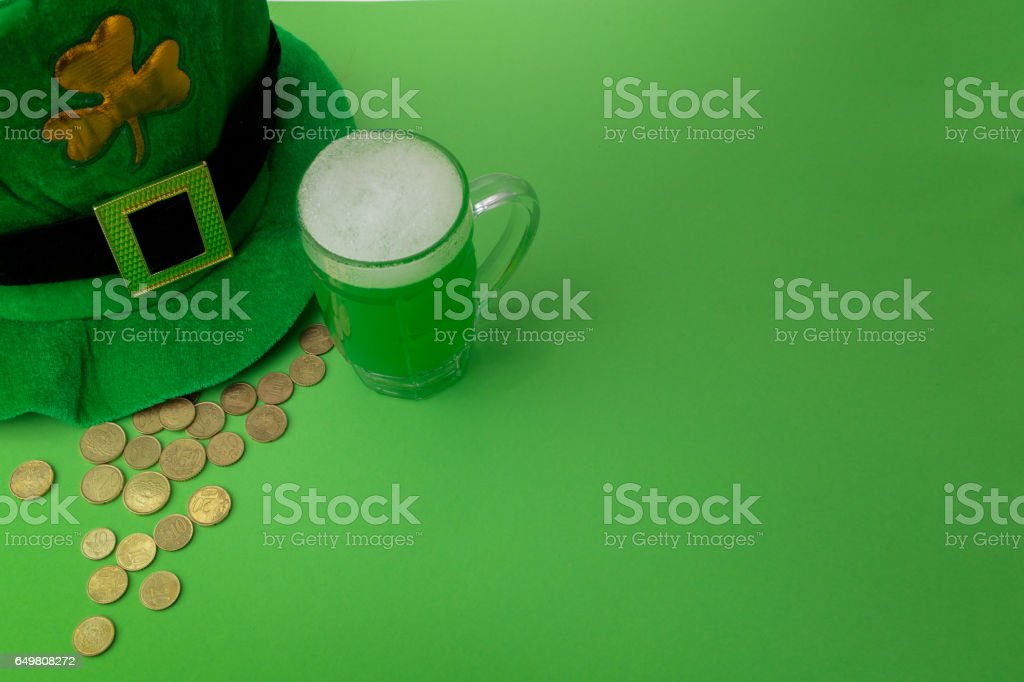 St Patrick's Day green beer with shamrock, pot with gold coins, horseshoe and Leprechaun hat against green background stock photo