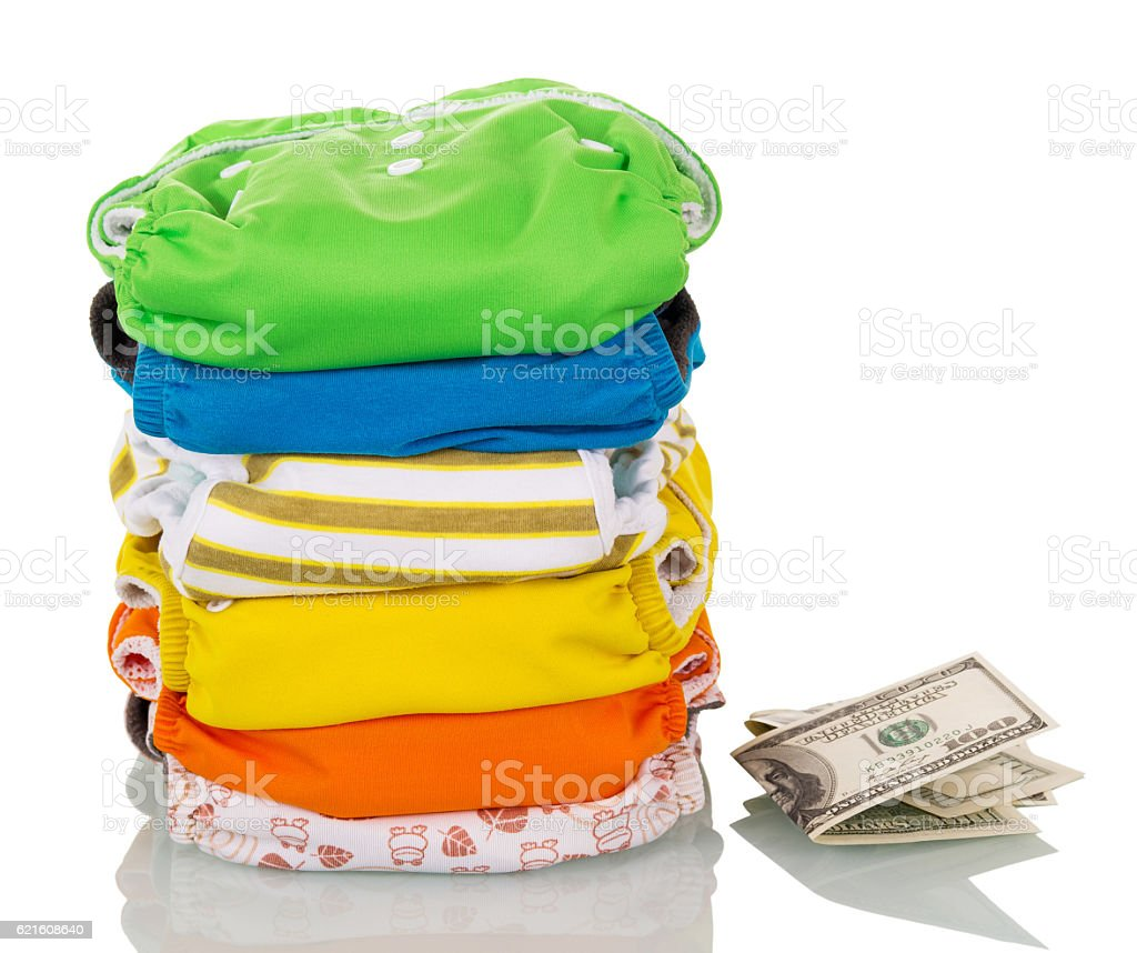 Stack modern eco-friendly diapers and money isolated on white. stock photo