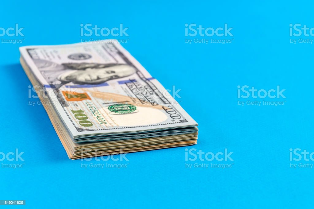 Stack of american dollar bills on the blue background. stock photo