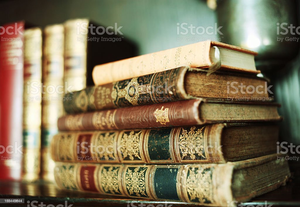 Stack of antique books on a shelf stock photo