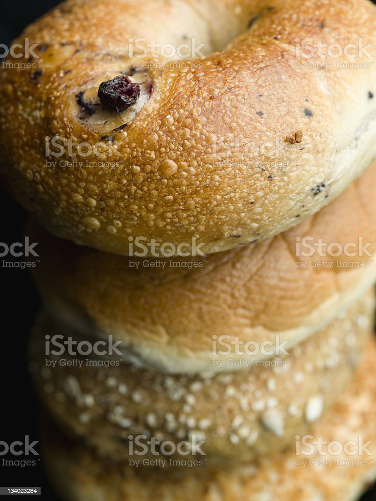 stack of assorted bagels on black background stock photo
