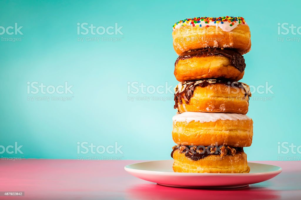 Stack of assorted donuts on pastel blue and pink background stock photo