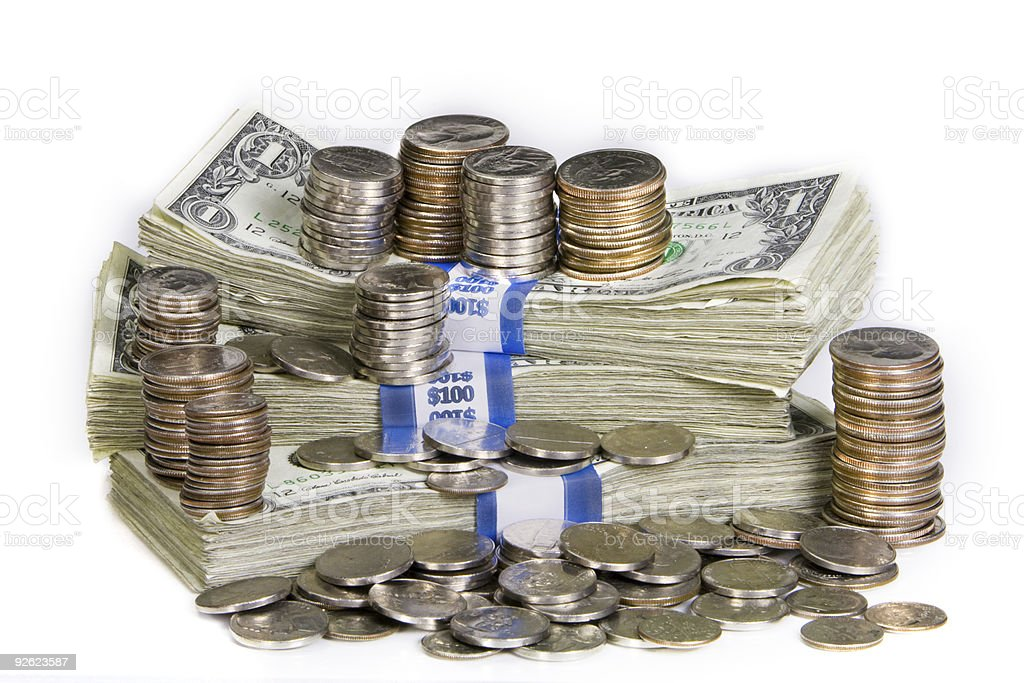 Stack of bank notes with piles of coins stock photo