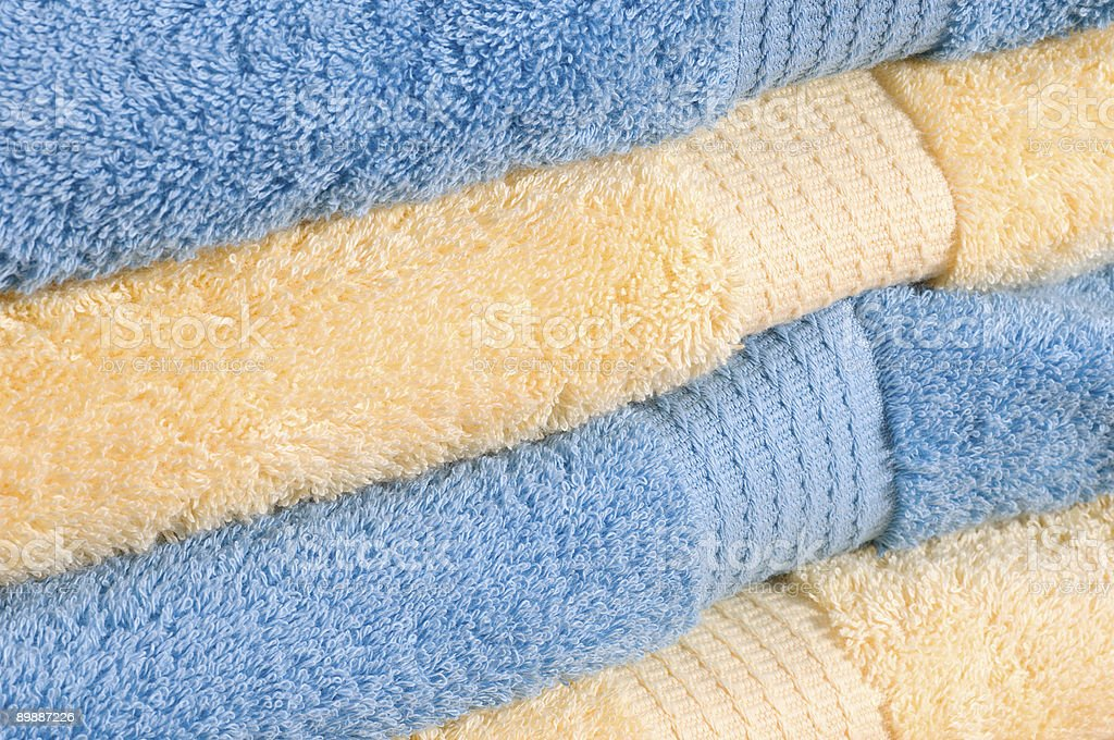 Stack of bath towels in yellow and blue stock photo