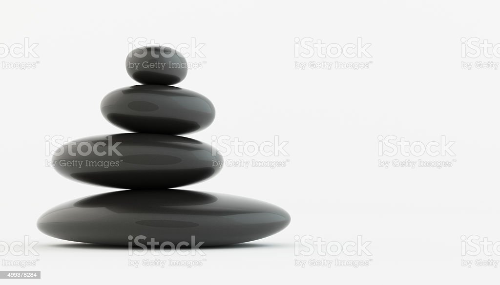 Stack of black zen stones on white floor. stock photo