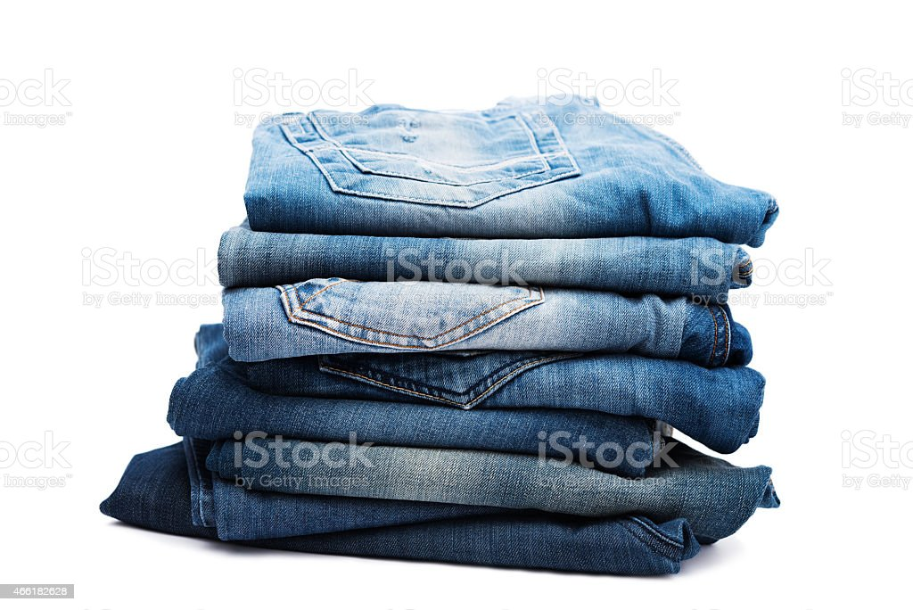 Stack of blue denim jeans on a white background stock photo