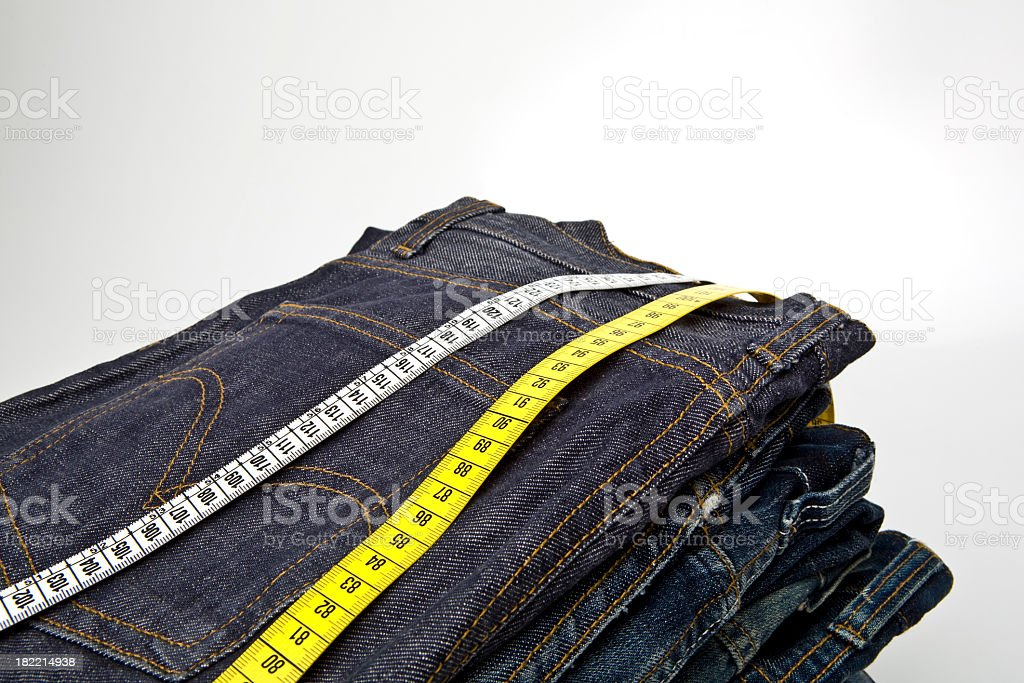 A stack of blue jeans with measuring tapes on top royalty-free stock photo