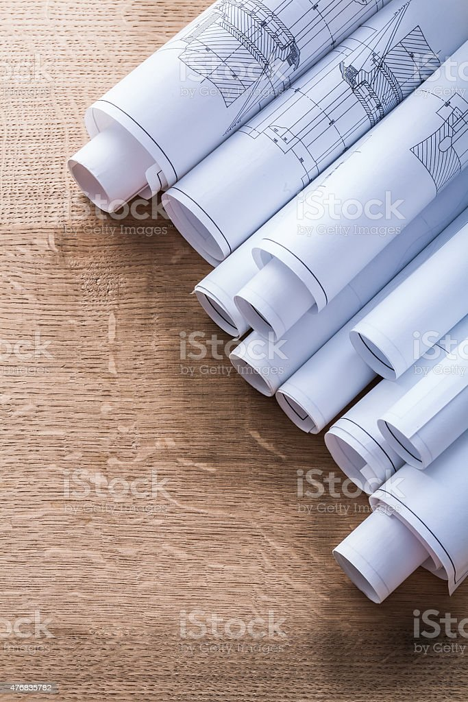 Stack of blueprint rolls on wooden oaken board maintenance conce stock photo