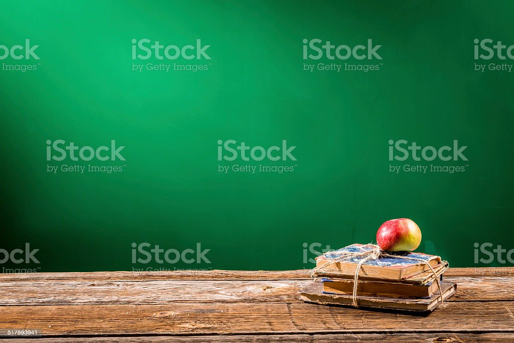 Stack of books and an apple in a classroom stock photo