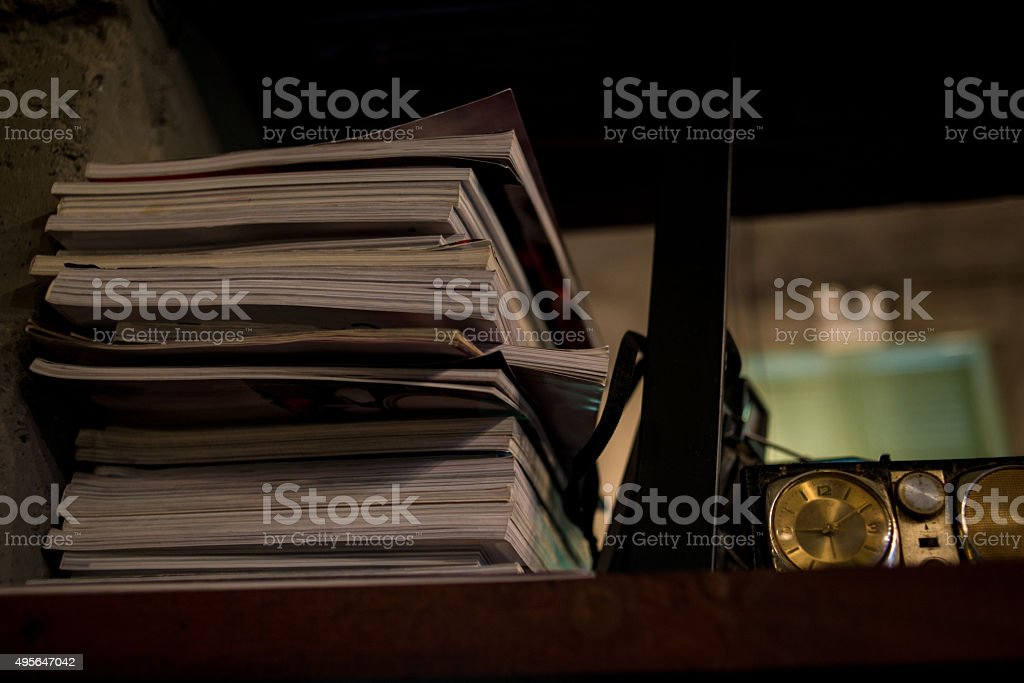 Stack of books and ancient alarm-clock on the dark background stock photo