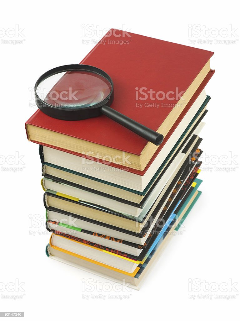 Stack of books and magnifying glass royalty-free stock photo