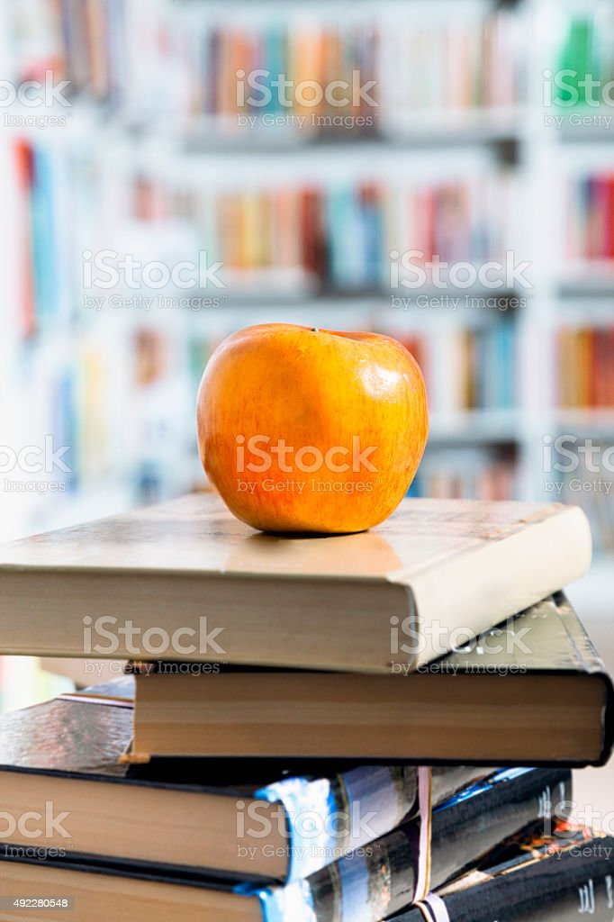 Stack of books in bookstore with apple on top stock photo