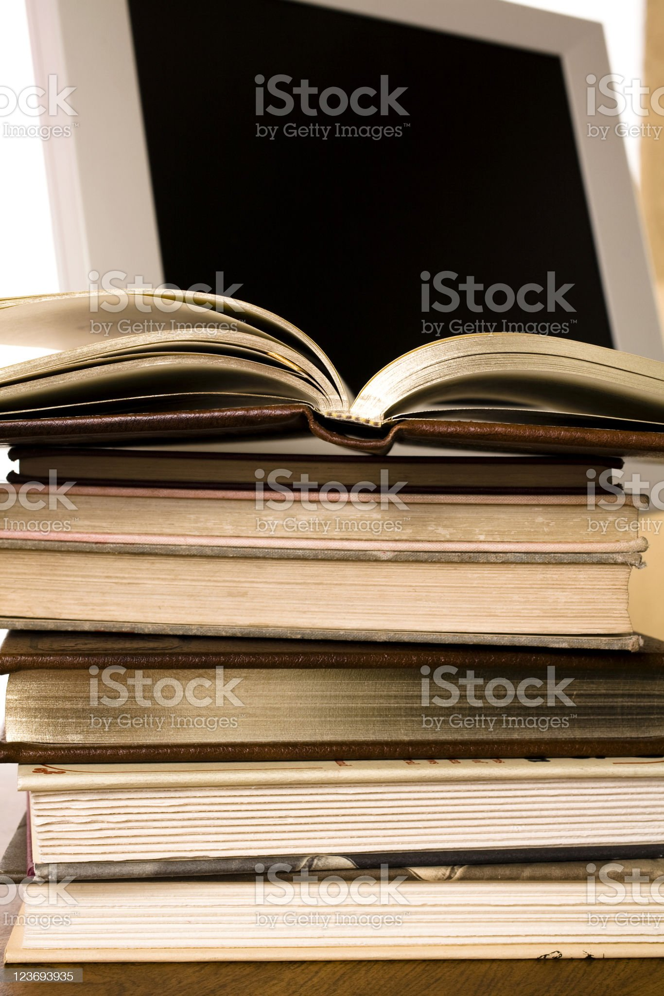 Stack of books in front the computer monitor royalty-free stock photo