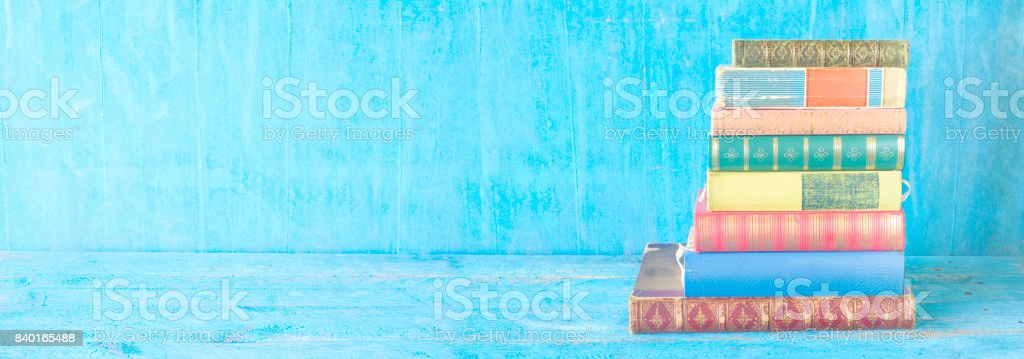 stack of books on blue grungy background, stock photo