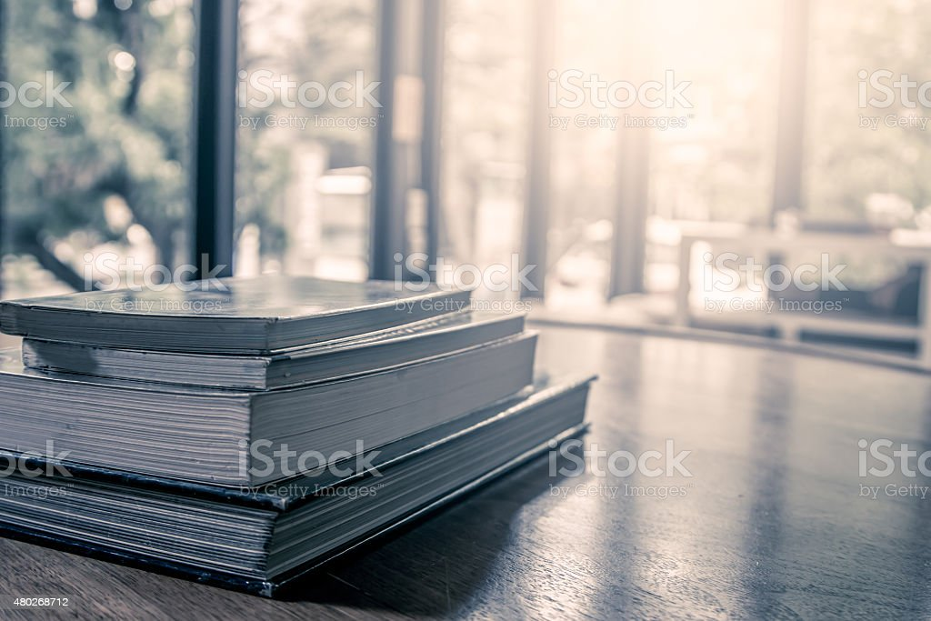 stack of books on wooden table in vintage color filter stock photo