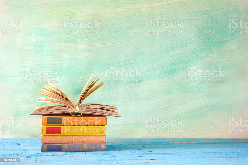 stack of books, one opened stock photo