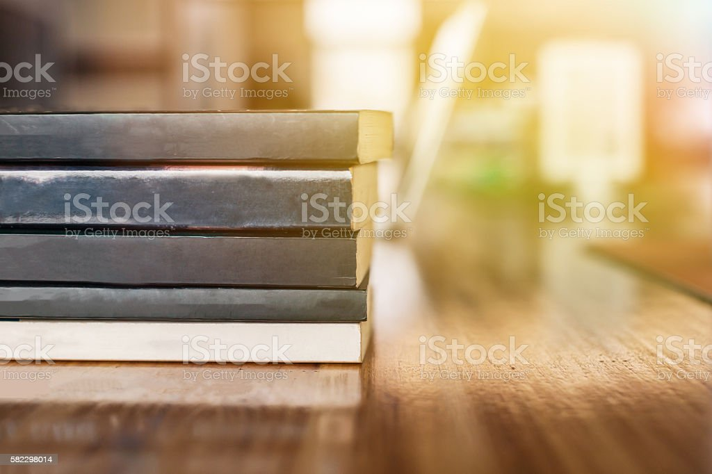 Stack of books piled up on working desk stock photo