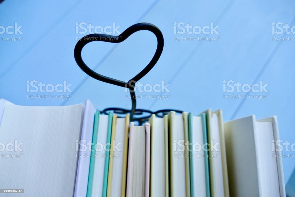 Stack of books with heart symbol behind stock photo