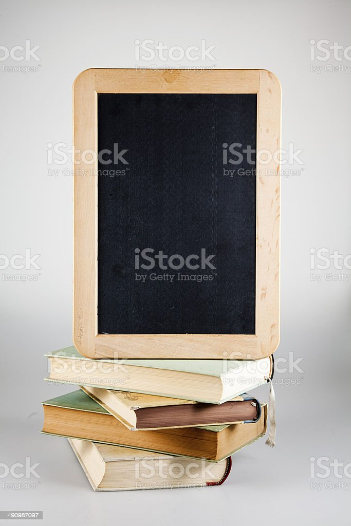 stack of books with school blackboard stock photo